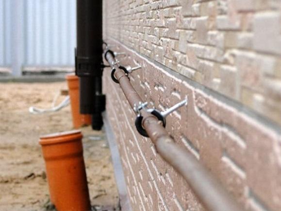 Горизонтальное крепление стальной трубы к фасаду с помощью хомутов